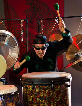 Eric Chun, Proud User and Endorser of Bag End Loudspeakers is shown playing the drums